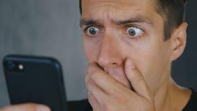 Mannen chockades av det dåliga meddelandet som han läste på hans smartphone Chockad och bedövad man för närbild stock video