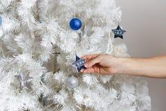 Mannen dekorerar en julgran royaltyfri fotografi