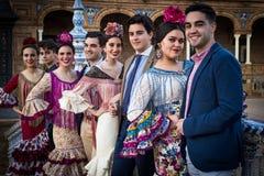 Mannen die met vrouwen met traditionele kleding stellen stock afbeelding