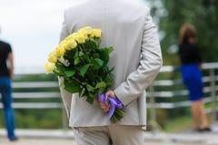 Mannen döljer en bukett av blommor bak hans baksida Royaltyfri Foto