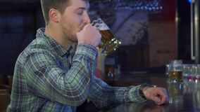 Mannen dricker öl på baren arkivfoton