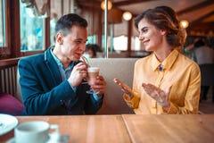 Mannen dricker en coctail från sugrör mot kvinna arkivbilder