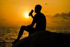 Mannen dricker från en flaska på gryning royaltyfri fotografi