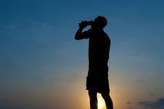 Mannen dricker från en flaska på gryning arkivfoton