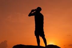 Mannen dricker från en flaska på gryning royaltyfria bilder