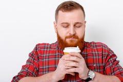 Mannen dricker kaffe för att vakna upp Royaltyfri Bild
