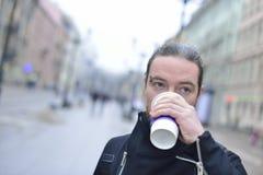 Mannen dricker kaffe i kallt väder utanför Royaltyfri Foto