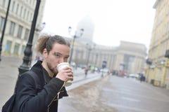 Mannen dricker kaffe i kallt väder utanför Arkivfoton