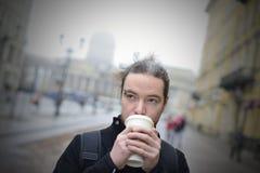 Mannen dricker kaffe i kallt väder utanför Arkivbilder