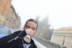 Mannen dricker kaffe i kallt väder utanför Royaltyfri Bild