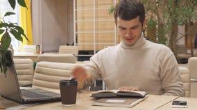 Mannen dricker kaffe på det funktionsdugliga navet lager videofilmer