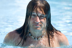 Mannen dyker upp från vatten, och vattnet kör ner hans framsida Arkivfoto