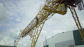 Mannen eller arbetaren stiger ned vid trappa från en lastningsbryggakran på industrianläggningen eller fabrik Färdigt arbete för  stock video