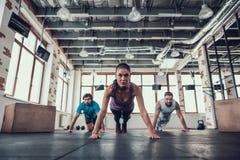 Mannen en Vrouw die Duw UPS in de Heldere Gymnastiek doen stock foto's