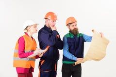 Mannen en vrouw in helmen, architecten op nadenkende gezichten Royalty-vrije Stock Afbeelding