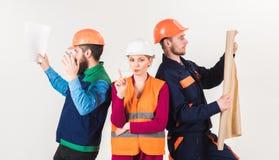 Mannen en vrouw in helmen onbezorgd met hamer en project, stock foto
