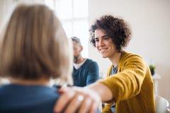 Mannen en vrouwen die in een cirkel tijdens groepstherapie, ondersteunend elkaar zitten stock foto