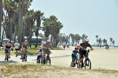 Mannen en vrouwen die op Tandems op het Strand van Venetië berijden Stock Fotografie