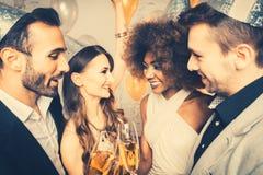 Mannen en vrouwen die partij vieren terwijl het clinking van glazen royalty-vrije stock afbeelding