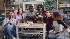 Mannen en vrouwen die videospelletje spelen die hebbend pret in vlakte bij moderne partij lachen stock video