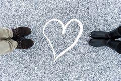 Mannen en vrouwen` s laarzen die zich bij abstract hartsymbool bevinden op asfalt behandelden zanderige sneeuwoppervlakte Ruwe sn Royalty-vrije Stock Foto's