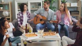 Mannen en vrouwenvrienden die de gitaar spelen en samen bij partij binnenshuis zingen stock footage