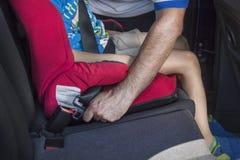 Mannen fäster en säkerhetsbälte till ett barn som sitter i ett bilsäte i baksätet royaltyfri fotografi