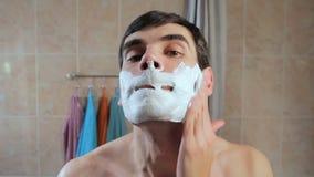 Mannen får raka skum på framsidan Grabben startar att raka framme av en spegel se henne lager videofilmer