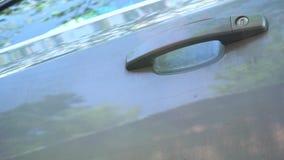 Mannen får ut ur bilen, stänger dörren med en tangent arkivfilmer