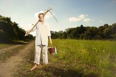 Mannen för äldre land kommer att meja gräs i solig dag arkivbild