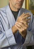 mannen för 3 händer smärtar wringing Arkivfoto