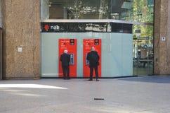 Mannen för affär två i svarta dräkter som att använda TA SIG EN TUPPLUR atm ut, sid byggnaden i Sydney arkivfoton