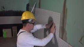 Mannen för den kompetenta arbetaren med den gula hjälmen lägger tegelplattor på väggen och blick på kameran