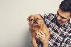 Mannen för hipsteren för Closeupståenden som isolerade den stiliga unga kysser hans röda hund för den bra vännen, ljus bakgrund P arkivfoto