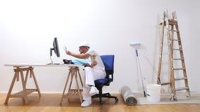 Mannen för husmålaren med blickar för en dator och förstoringsglaspå färgprövkopior och söker internet, e-kommers och shoppar mål arkivfilmer