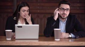 Mannen för kaffeavbrottet som distraheras av påringning och flickan, drar hans uppmärksamhet till bärbara datorn arkivfilmer