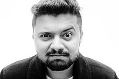 Mannen för närbildstudioståenden förvirrade ansiktsuttryck på vit arkivfoto