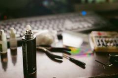 Mannen förbereder den elektroniska cigaretten för spolen som röker smaklig vapefruktsaft arkivfoto