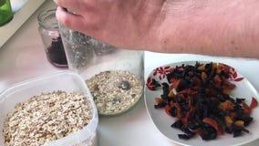 Mannen förbereder ingredienserna för mysli hemma Han klipper torkat - frukt med sax Timelapse arkivfilmer