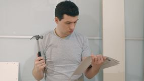 Mannen förbereder sig att montera möblemang arkivfilmer
