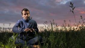 Mannen förbereder trä-ull med jaktkniven för att starta brand på solnedgången på fältet raka trä överlevnadbegrepp stock video