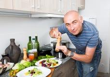 Mannen förbereder två sallader och fyller dem med peppar på hem- kitc Fotografering för Bildbyråer