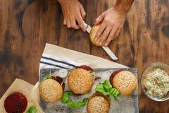 Mannen förbereder vegetariska hamburgare med olika toppningar arkivbild