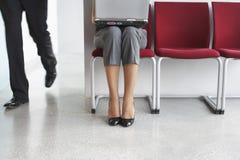 Mannen förbigår kvinnan med bärbara datorn på stol i korridor royaltyfria bilder