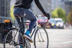 Mannen föredrar en ekonomisk väg att resa, och ritter cyklar på stadsgatan royaltyfria bilder