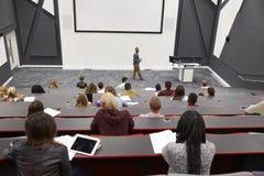 Mannen föreläser studenter i föreläsningsteatern, baksidaradplatsen POV Royaltyfri Fotografi