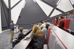Mannen föreläser studenter i föreläsningsteatern, första radenplatsen POV Arkivfoto