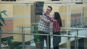 Mannen förklarar kvinnaröntgenstrålen av olik typ av sacrumen i korridor i universitet stock video