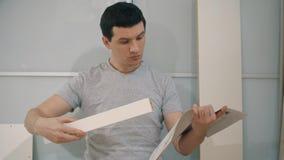 Mannen försöker att montera möblemang stock video