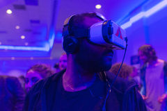Mannen försöker hörlurar med mikrofon för det virtuell verklighetSamsung kugghjulet VR Arkivbild